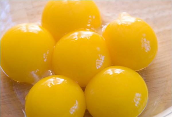 Hướng dẫn làm kem tươi - đập trứng gà lấy phần lòng đỏ trứng khấy đều và cho vào nồi sữa