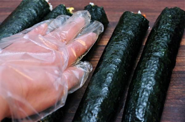 Cơm cuộn - xao dầu mè vào lòng bàn tay và xoa khắp lên trên những miếng kimbap