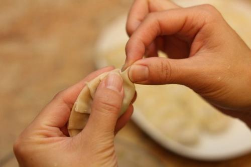 Dùng ngón trỏ vá ngón cái bóp nhẹ từng mép bánh và dán chồng lên nhau