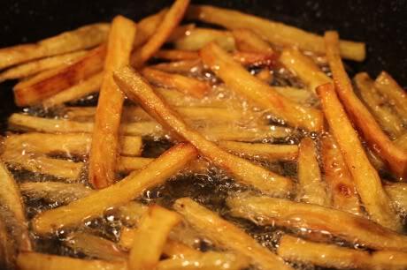 Chiên khoai lang trong chảo ngập dầu cho đến khi khoai vàng