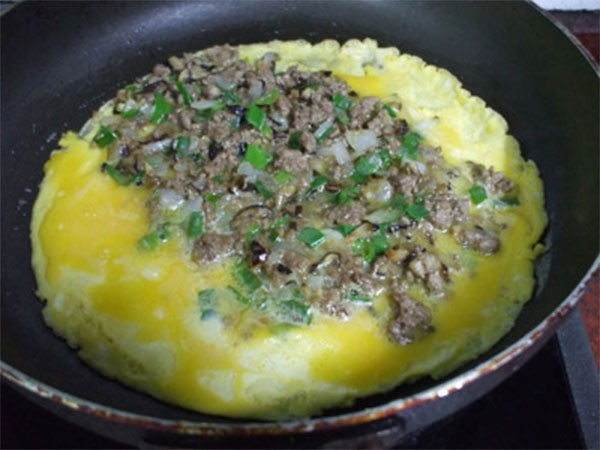 Cho phần thịt đã xào chín vào phần trứng đang rán - cach lam trung cuon