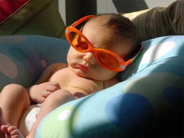 Đặt trẻ tắm nắng ở tư thế thoải mái và chú ý bảo vệ vùng mắt cho trẻ - cách tắm nắng cho trẻ
